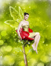 Gorgeous young woman as spring fairy sitting on red flower on green background Royalty Free Stock Photos