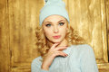 Gorgeous young woman with blond ringlets in a green knitted winter outfit over light brown Royalty Free Stock Photo