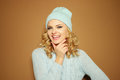 Gorgeous young woman with blond ringlets in a green knitted winter outfit over light brown smiling Royalty Free Stock Photos