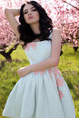 gorgeous young woman in elegant dress posing in garden with blossom peach trees Royalty Free Stock Photo