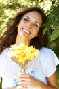 Gorgeous young woman holding yellow flowers Royalty Free Stock Images
