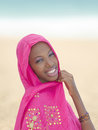 Gorgeous young woman wearing a pink veil at the beach