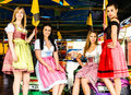 Gorgeous young women at german funfair joyful and attractive oktoberfest with traditional dirndl dresses and bumper car in the Stock Photography
