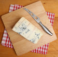 Gorgonzola blue cheese on cheeseboard with knife Stock Photography