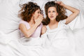 Gossip friendship happiness two smiling girls whispering white bed from above Royalty Free Stock Photos
