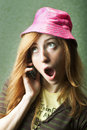 Gossiping funny young woman in pink hat on mobile phone Stock Images