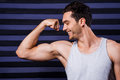 He got perfect body muscular young man in tank top examining his biceps and smiling while standing against striped background Royalty Free Stock Photo