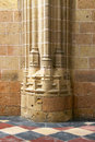A gothic column base, with a tiles floor, against a wall Royalty Free Stock Photo