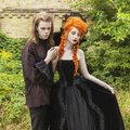Gothic couple in a halloween costume. Pale undead vampires in dark victorian clothes. Redhead woman in black carnival dress. Royalty Free Stock Photo