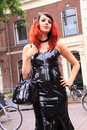 Gothic fetish girl street fashion black pvc dress beautiful with red hair wearing a long tight during the festival summer darkness Stock Image