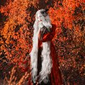 Gothic halloween coat. Young medieval blonde queen autumn background. Lady with gray hair. Vampire with pale skin. Outfit for