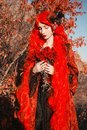 Gothic halloween coat. Young queen with flowers bouquet on autumn background. Lady with red hair. Vampire with pale skin. Ooutfit Royalty Free Stock Photo