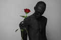 Gothic and Halloween theme: a man with black skin holding a red rose, black death  on a gray background in studio Royalty Free Stock Photo