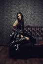 Gothic lady portrait of girl in black latex dress sitting on a sofa Stock Photo