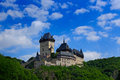 Gothic royal castle Karlstejn in green forest during summer with blue sky and white clouds, Central Bohemia, Czech republic, Europ Royalty Free Stock Photo
