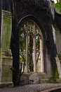 Gothic window in the black wall and the gravestone under it Royalty Free Stock Photo