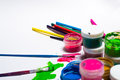 Gouache paint, brushes, and colored pencils on a light background Royalty Free Stock Photo