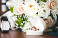 Gouden trouwringen in witte giftdoos met boeket en horloge op achtergrond Royalty-vrije Stock Afbeeldingen