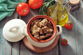 Goulash in a ceramic pot with tomatoes spices and rosemary on wooden background Stock Photography