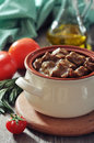 Goulash in a ceramic pot with tomatoes spices and rosemary on wooden background Stock Images