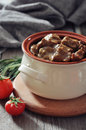 Goulash in a ceramic pot with tomatoes spices and rosemary on wooden background Royalty Free Stock Image