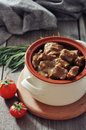 Goulash in a ceramic pot with tomatoes spices and rosemary on wooden background Stock Image