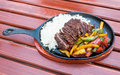 Gourmet beef dish dinner meal served in a frying pan with steamed vegetables Stock Photography