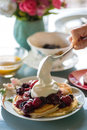 Gourmet breakfast of pancakes, fruit puree and whip cream Royalty Free Stock Photo