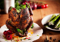 Gourmet grilled whole beer can chicken on a white plate close up with herbs and spices served top of wooden kitchen table Royalty Free Stock Photography