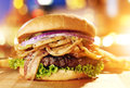 Gourmet hamburger with fried onion straws and cityscape background Stock Photos
