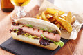 Gourmet hot dog on slate board with rustic fries Royalty Free Stock Photos