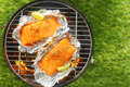 Gourmet salmon steaks grilling on a barbecue in tin foil wrappers garnished with leomon wedges overhead view Royalty Free Stock Images