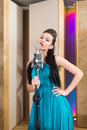 Grace girl with red lips holding a microphone and singing in recording studio Stock Photos