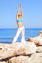 Graceful girl ashore epidemic deathes concerns with yoga the Royalty Free Stock Photo