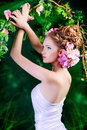 Graceful girl beautiful young woman standing under an arch of flowers and overgrown loach magic of the spring Stock Photo