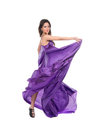 Graceful girl in flying purple silk dress Stock Images
