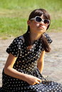 Graceful girl portrait young fashionable brunette child in polka dotted dress sitting at the street looks up Stock Photography
