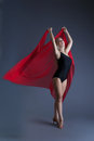 Graceful young girl dancing with red chiffon on gray background Royalty Free Stock Images