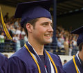 Graduate in cap and gown with honor cords Stock Photography