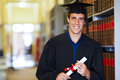 Graduate graduation gown handsome male wearing in library Stock Photo
