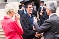 Graduate handshaking grandfather cheerful male with his Royalty Free Stock Photo