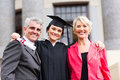 Graduate with parents beautiful young female at ceremony Stock Images