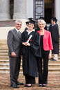 Graduate with parents portrait of young girl standing at graduation ceremony Stock Photos
