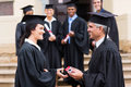 Graduate receiving diploma cheerful young from dean Royalty Free Stock Photo