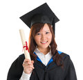 Graduate student portrait of happy asian female in gown holding graduation diploma isolated on white background Royalty Free Stock Photo
