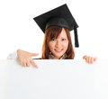 Graduate student showing blank placard portrait of smiling asian female in gown space on banner isolated on white background Royalty Free Stock Photo