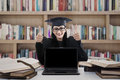 Graduate woman giving thumbs up in library female with empty blank screen laptop shot Royalty Free Stock Images