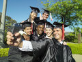 Graduates in caps and gowns taking photograph of themselves outdoors Stock Image