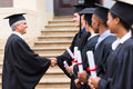 Graduates handshaking dean group of cheerful in line with Royalty Free Stock Photography