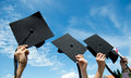 Graduates many hand holding graduation hats on background of blue sky Royalty Free Stock Photos
